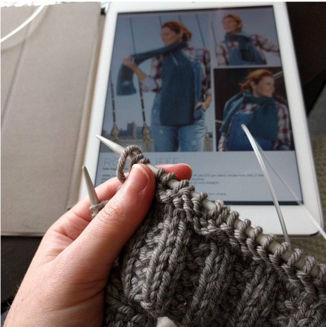 In foreground, someone is knitting a grey scarf. In background is an iPad with the scarf pattern.