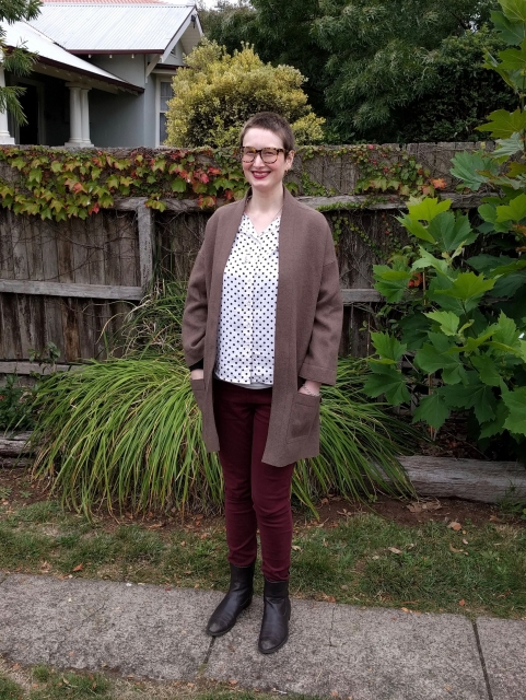 A woman stands against a garden fence. She wears a spotted button up shirt, maroon skinny jeans, brown boots and an oversized brown wool open coat.