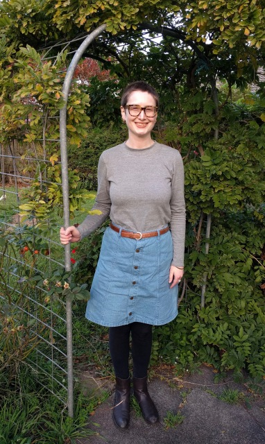 Woman stands in garden archway. She wears a grey turtleneck skivvy, denim skirt and boots.