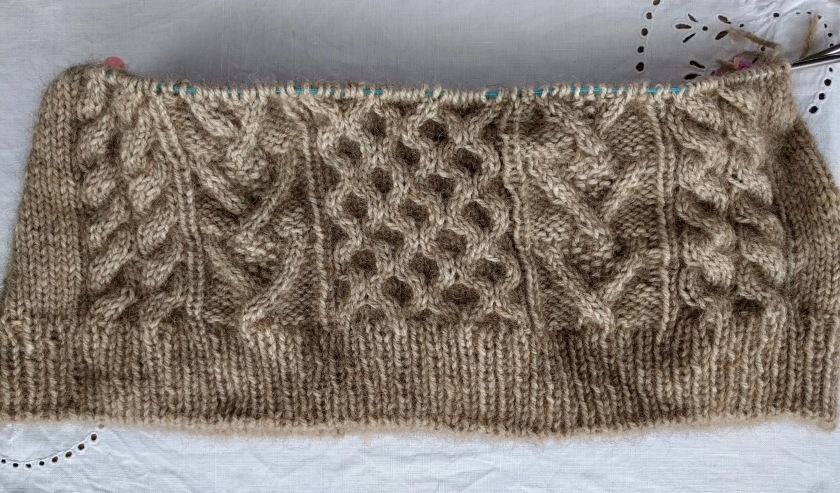 An image of some brown, cabled, handknitting, laid flat on a white surface.