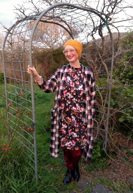 A photograph of a woman standing in a garden arch. She wears a long check cardigan, black floral dress, burgundy velvet leggings and a yellow hand knit hat. She is smiling.