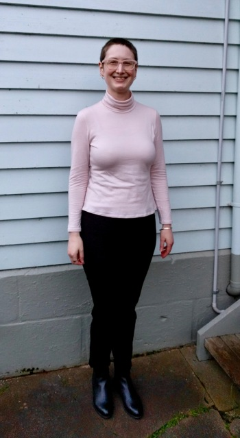 Woman stands in front of weatherboard house. She wears pink merino long sleeve tee, black pants and ankle boots.