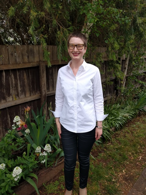 A woman stands against a garden fence. She wears a white button up shirt and black coated jeans.