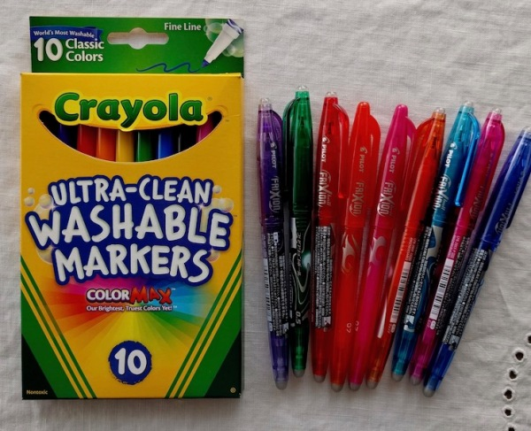 Packet of Crayola Ultra Clean Washable Markers and several Pilot Frixion pens.