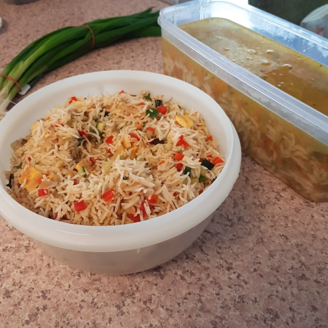 A kitchen bench with huge plastic containers filled with fried rice and chicken soup cooked by a support worker, in front of a bunch of spring onions.
